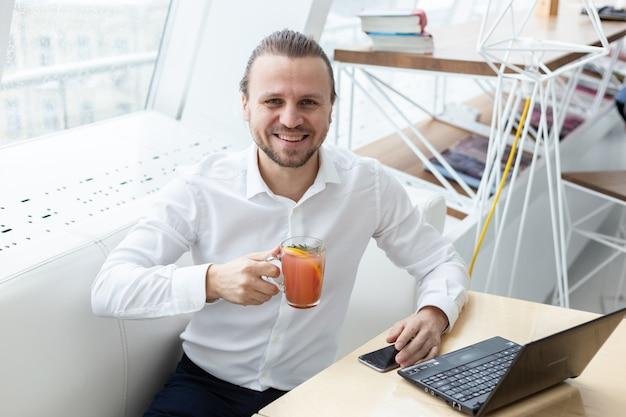 Un homme heureux assis à la table tenant une tasse de boisson à côté de la fenêtre dans un intérieur moderne blanc. Photo Premium