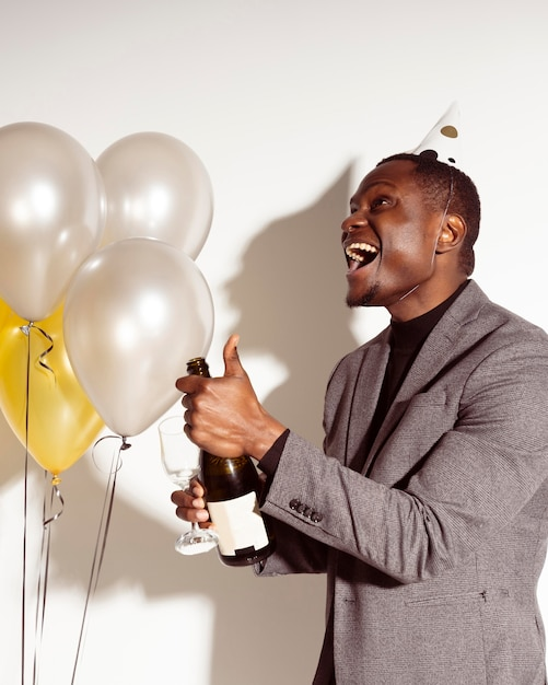 Homme Heureux Sur Le Côté Ouvrant Une Bouteille De Champagne Photo gratuit