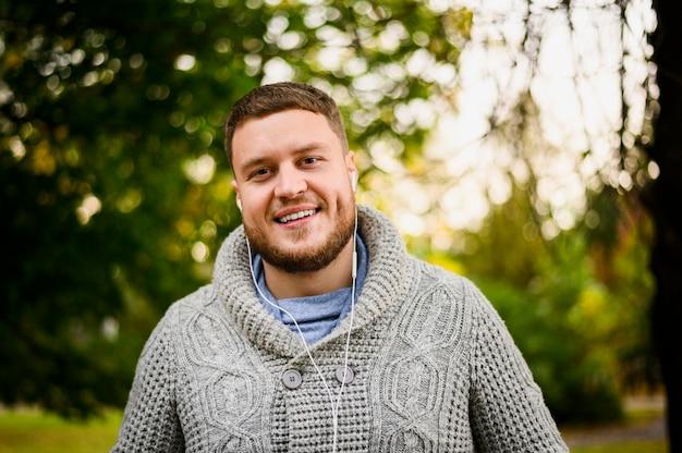 Homme heureux avec des écouteurs, souriant à la caméra Photo gratuit