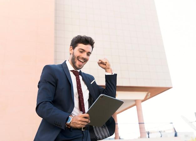 Homme heureux à faible angle exprimant la victoire Photo gratuit