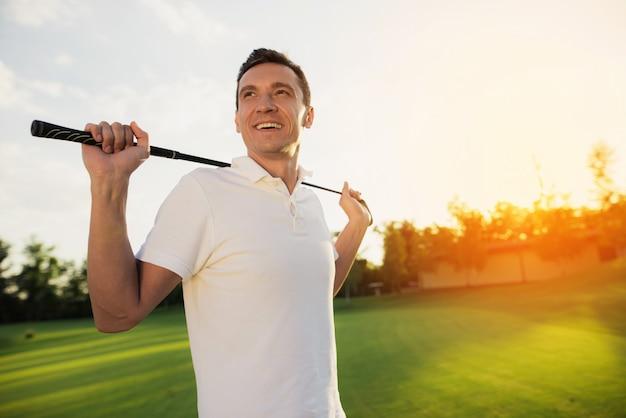 Homme heureux joueur en blanc tenant club de golf. Photo Premium