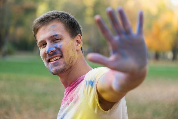 Homme heureux avec main colorée et visage à holi Photo gratuit