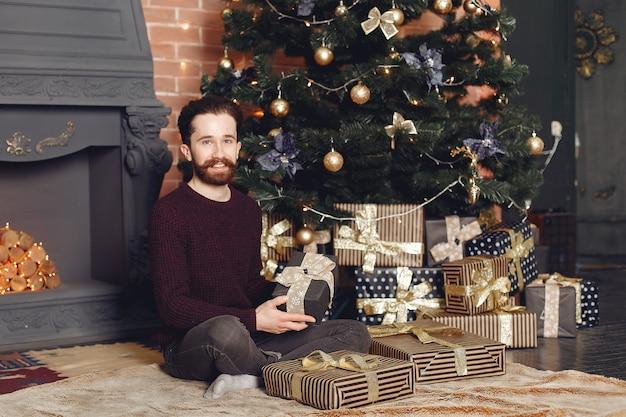 Homme Heureux En Pull Rouge. Guy Devant La Cheminée. Mâle Sur Le Fond De L'arbre De Noël. Photo gratuit