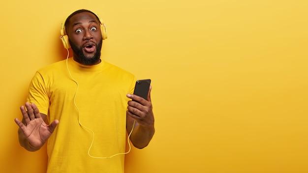 Un Homme Heureux Surpris Et Insouciant A La Peau Foncée, Des Poils épais, écoute De La Musique Dans Des écouteurs, Tient Un Téléphone Intelligent Moderne Photo gratuit