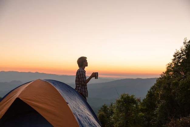 Homme heureux avec une tasse de café rester près de la tente autour des montagnes sous la lumière du coucher du soleil Photo gratuit