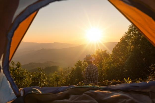 Homme heureux avec une tasse de café rester près de la tente autour des montagnes Photo gratuit
