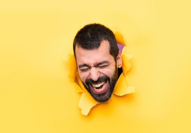 Homme heureux à travers un trou de papier Photo Premium