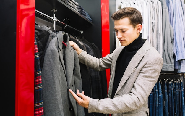 Homme heureux vérifiant l'étiquette de prix du manteau en magasin Photo gratuit