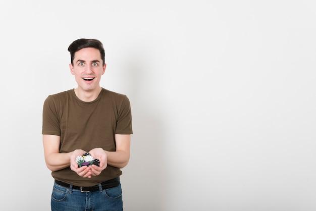 Homme heureux vue de face avec des jetons de poker Photo gratuit