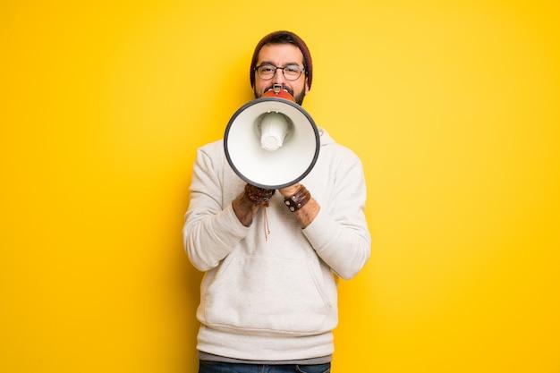 Homme hippie avec des dreadlocks criant à travers un mégaphone pour annoncer quelque chose Photo Premium