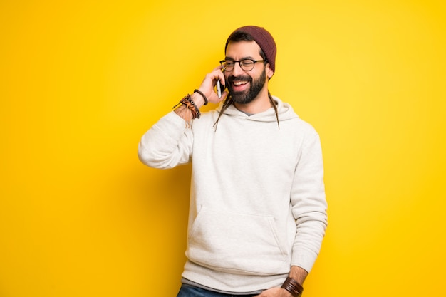 Homme hippie avec des dreadlocks maintenant une conversation avec le téléphone portable Photo Premium