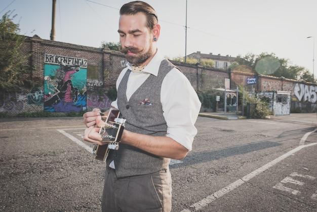 Homme de hipster belle grosse moustache jouant de mandoline Photo Premium