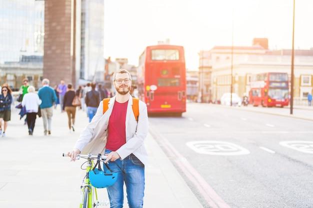 Homme hipster marchant sur le pont de londres et tenant son vélo fixe Photo Premium