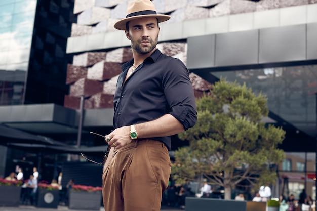 Homme de hipster musclé tanné brutal posant dans les rues Photo Premium