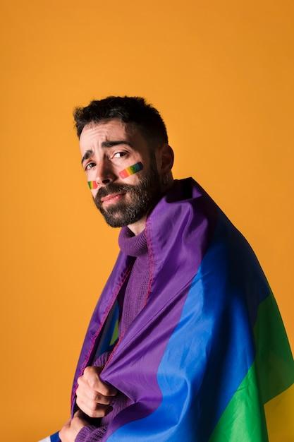 Homme homosexuel émotionnel enveloppé dans le drapeau arc-en-ciel lgbt Photo gratuit