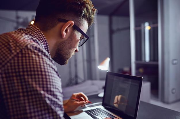 Un homme indépendant barbu avec un ordinateur portable fonctionne Photo Premium