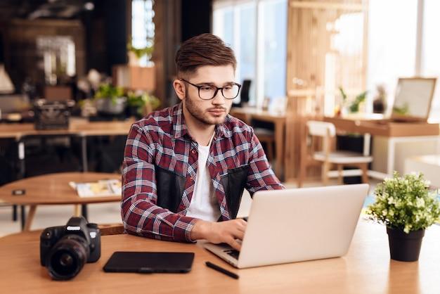 Homme indépendant tapant sur un ordinateur portable assis au bureau. Photo Premium