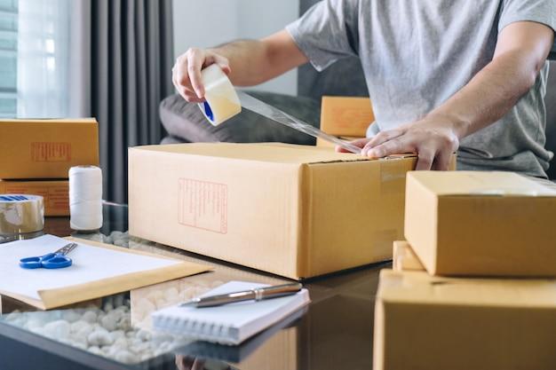 Homme indépendant travaillant dans une pme pour l'emballage de ses colis sur le marché en ligne Photo Premium