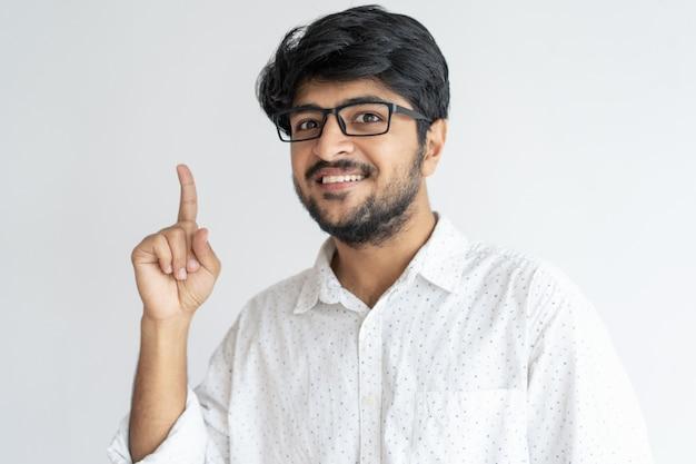 Homme indien souriant pointant vers le haut et regardant la caméra Photo gratuit
