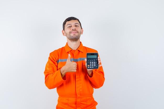 Homme Industriel Tenant La Calculatrice, Montrant Le Pouce Vers Le Haut En Uniforme Et à La Recherche De Joie. Vue De Face. Photo gratuit