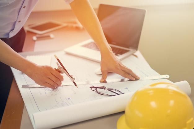 Homme ingénieur travaillant avec un ordinateur portable et plans de croquis d'un projet de construction Photo Premium