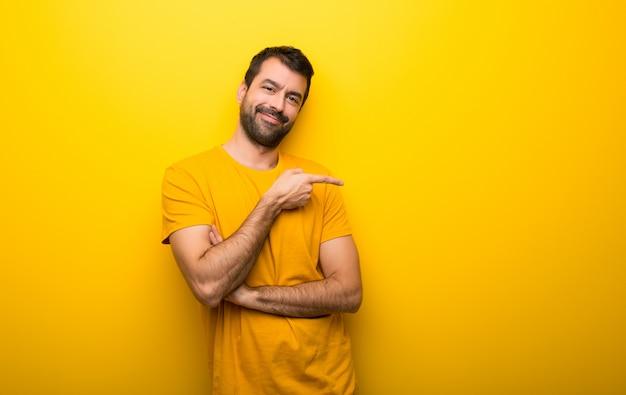 Homme isolé de couleur jaune vif, pointant le doigt sur le côté en position latérale Photo Premium