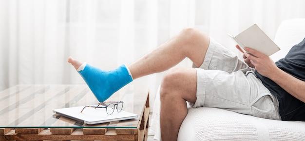 Un Homme Avec Une Jambe Cassée Dans Un Plâtre Lit Des Livres Dans L'entraîneur Photo Premium