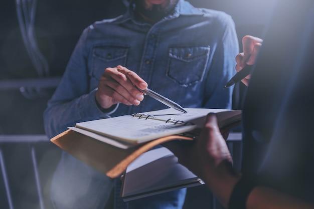 Homme en jeans donne des conseils sur le travail dans un cahier avec des collègues au bureau. Photo Premium