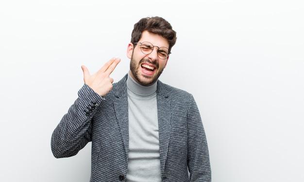 Homme Jeune Dirigeant à La Recherche De Malheureux Et Stressé, Geste De Suicide Faisant Signe De L'arme à Feu Avec La Main, Pointant Vers La Tête Contre Le Mur Blanc Photo Premium