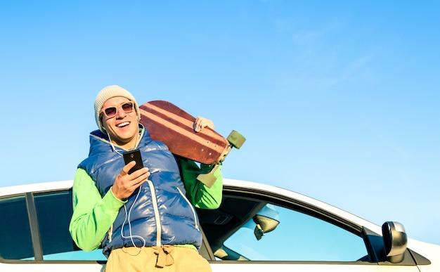 Homme jeune hipster avec musique écoute smartphone à côté de sa voiture Photo Premium