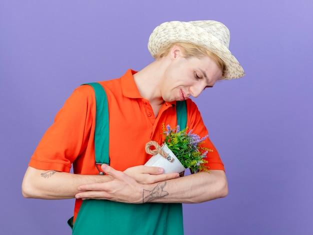 Homme Jeune Jardinier Portant Combinaison Et Chapeau Tenant Une Plante En Pot Comme Bébé Photo gratuit