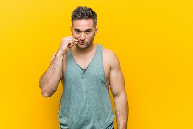 Homme jeune de remise en forme contre un jaune avec les doigts sur les lèvres gardant un secret. Photo Premium