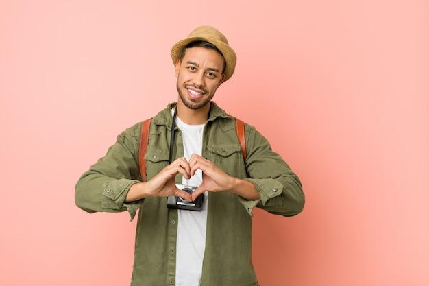 Homme Jeune Voyageur Philippin Souriant Et Montrant Une Forme De Coeur Avec Les Mains. Photo Premium