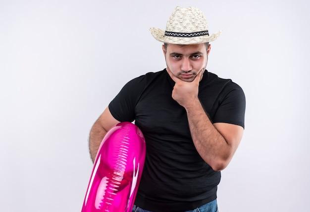 Homme Jeune Voyageur En T-shirt Noir Et Chapeau D'été Tenant Un Anneau Gonflable Avec Un Visage Fronçant Les Sourcils Perplexe Debout Sur Un Mur Blanc Photo gratuit