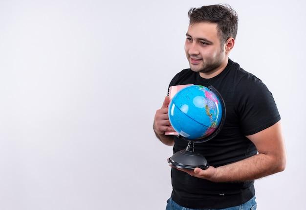 Homme Jeune Voyageur En T-shirt Noir Tenant Un Globe à Côté Avec Sourire Sur Le Visage Debout Sur Un Mur Blanc Photo gratuit