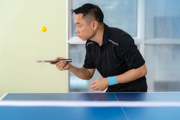 Homme jouant au tennis de table avec raquette et balle dans une salle de sport Photo Premium