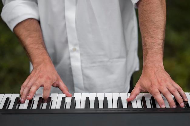 Homme Jouant Des Claviers De Synthétiseur à L'extérieur Close-up Photo gratuit