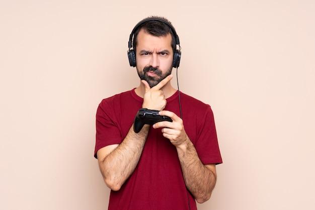 Homme Jouant Avec Un Contrôleur De Jeu Vidéo Sur La Pensée De Mur Isolé Photo Premium