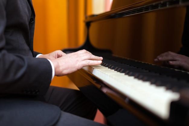 Homme jouant du piano. aucun visage montré Photo Premium