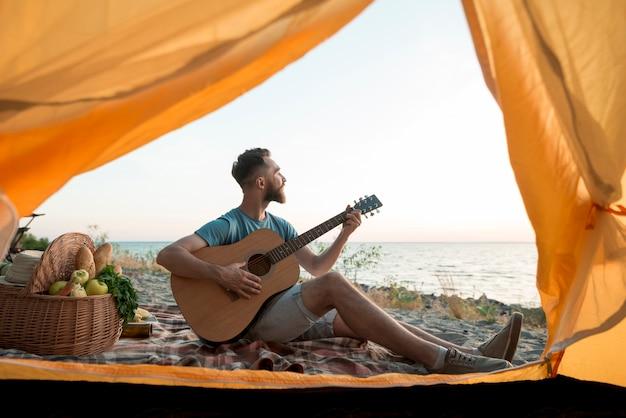 Homme jouant de la guitare devant la tente Photo gratuit