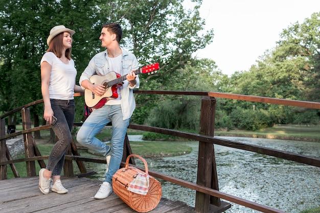 Homme jouant de la guitare à sa fille sur un pont Photo gratuit