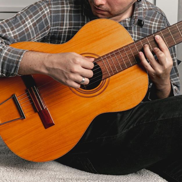 Homme jouant de la vieille guitare acoustique Photo gratuit