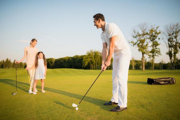 Un homme joue au golf avec son passe-temps pour femme et enfant. Photo Premium