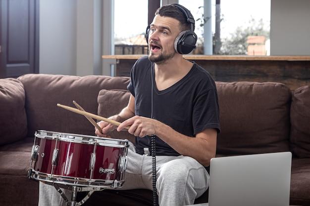 Un Homme Joue Du Tambour Et Regarde L'écran Du Portable. Le Concept De Cours De Musique En Ligne, Cours De Vidéoconférence. Photo gratuit