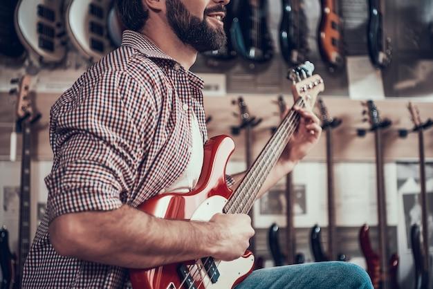 L'homme joue à la guitare électrique rouge dans le magasin d'instruments. Photo Premium