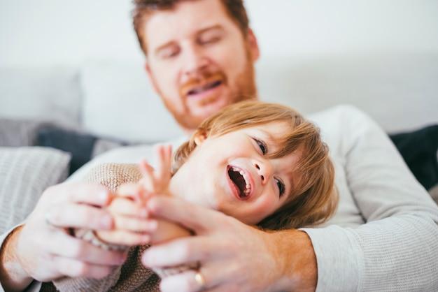Homme, jouer, rire, fils, sur, sofa Photo gratuit