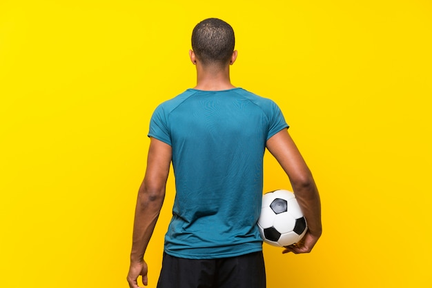 Homme de joueur de football afro-américain sur jaune isolé Photo Premium