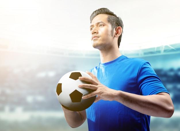 Homme de joueur de football asiatique en maillot bleu tenant le ballon sur le terrain de football Photo Premium