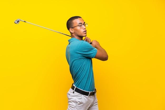 Homme de joueur de golfeur afro-américain sur fond jaune isolé Photo Premium