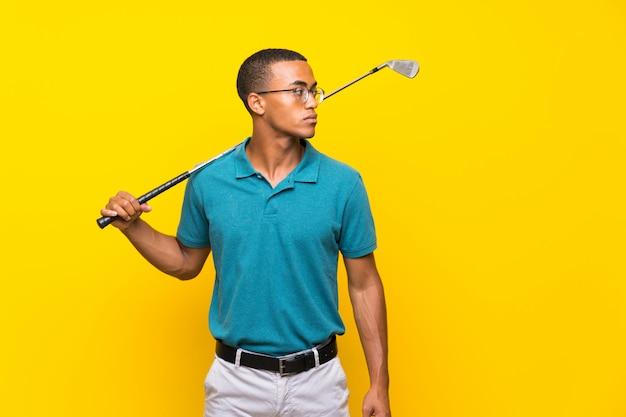 Homme de joueur de golfeur afro-américain sur jaune isolé Photo Premium